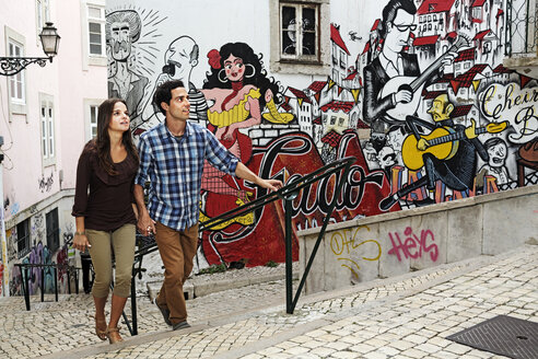 Portugal, Lisboa, Mouraria, young couple in front of mural painting - BI000021