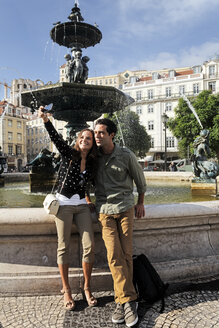 Portugal, Lisboa, Baixa, Rossio, Praca Dom Pedro IV, young couple photographing themself in front of a fountain - BIF000012