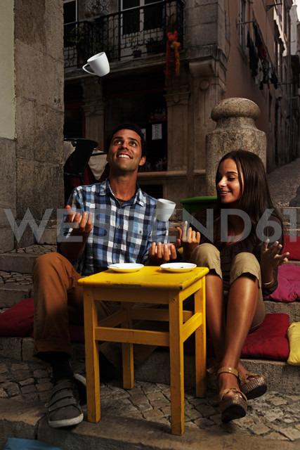Portugal, Lisboa, Bairro Alto, young couple sitting at street cafe at dusk - BIF000002