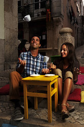 Portugal, Lisboa, Bairro Alto, young couple sitting at street cafe at dusk - BIF000002