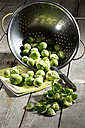Brussel sprout in colander, kitchen towel on wooden table - MAEF007397