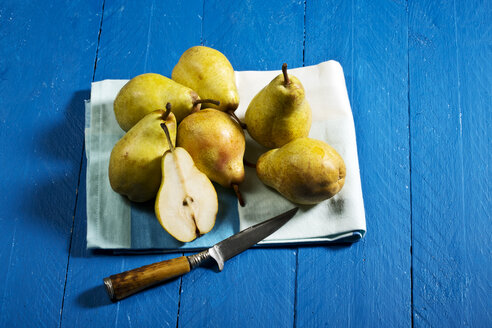 Williams pears and knife on blue wooden table - MAEF007416