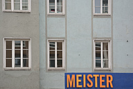 Germany, Bavaria, Munich, part of grey house front with windows and sign - AX000575