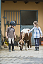 Germany, NRW, Korchenbroich, Boy and Girl at riding stable with mini shetland pony - CLPF000010