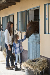Germany, NRW, Korchenbroich, Woman and girl stroking horse in stable - CLPF000004
