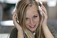 Portrait of smiling young woman with headphones - DRF000294