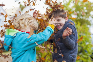 Two little boys throwing autumn leaves - MJF000435
