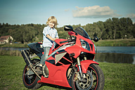 Germany, Saxony, Mulde River, little boy sitting on red motorcycle - MJ000420
