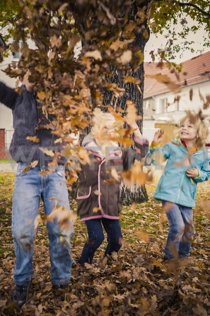 Three children throwing autumn leaves - MJF000415