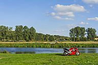 Germany, Saxony, Mulde River, red motorcycle parking on meadow - MJ000407