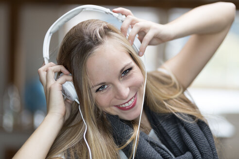Portrait of smiling young woman with headphones, close-up - DR000305