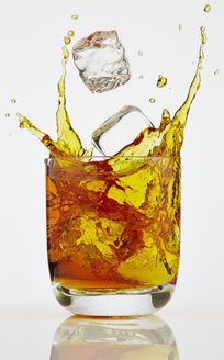 Ice cube splashing into glass of Whiskey - AKF000269