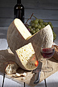 French Bethmale cheese, grapes, baguette and red wine glass and bottle - CS020376