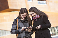 Two young women using digital tablet outdoors - DISF000228