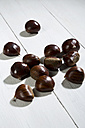 Spanish chestnuts (Castanea sativa) on white wooden table - MAEF007472