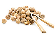Walnuts (Juglans regia) and nutcracker on white background - MAEF007470