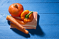 Hokkaido pumpkin, carrots and paprika on blue wooden table - MAEF007477