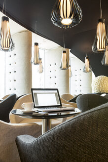 Poland, Warsaw, laptop, smartphone and coffee cup at lounge of hotel - MLF000234