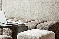 Poland, Warsaw, laptop, smartphone and coffee cup at lounge of hotel - MLF000239