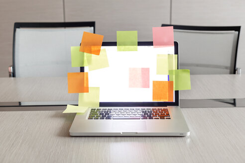 Opened laptop with plenty of coloured adhesive labels on conference table - MLF000212