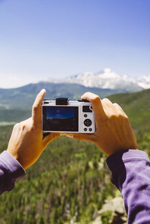 USA, Colorado, Rocky Mountain National Park, Woman taking a picture of Longs Peak and Mount Meeker - MBE000920