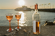 Germany, Bavaria, Nonnenhorn, Bottle of wine and glasses on wall at shipping pier - SH001072