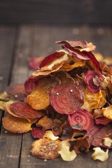 Roasted vegetable chips made of parsnips, sweet potatoes, beetroots, carrots and turnips on wooden table - ECF000398