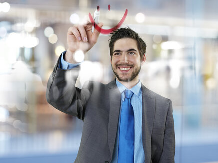 Portrait of businessman drawing smile on glass pane - STKF000710