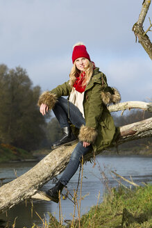 Young woman sitting at tree trunk - MAE007536