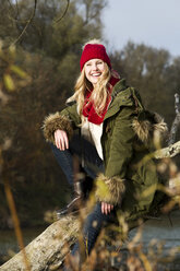 Smiling young woman sitting at tree trunk - MAE007535