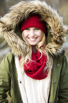 Portrait of young woman wearing woolly hat and hooded jacket - MAE007533