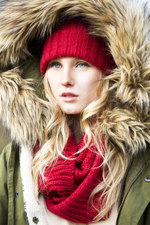 Portrait of young woman wearing woolly hat and hooded jacket - MAE007532