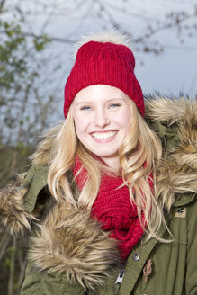 Portrait of smiling young woman wearing red wool cap - MAE007542