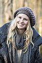 Portrait of young smiling woman wearing wool cap - MAE007528