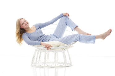 Blond young woman relaxing in papasan chair - MAEF007547