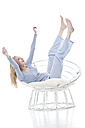 Blond young woman cheering in papasan chair - MAEF007548