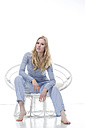 Blond young woman relaxing in papasan chair - MAEF007553