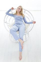 Blond young woman relaxing in papasan chair - MAEF007557