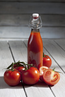 Homemade tomato juice on wooden table - CSF020482