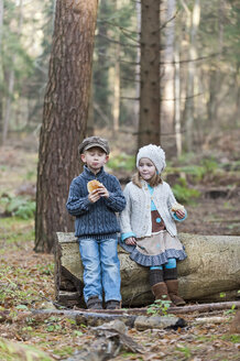 Germany, North Rhine-Westphalia, Moenchengladbach, Scene from fairy tale Hansel and Gretel, brother and sister eating bread in the woods - CLPF000023