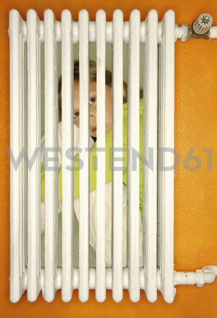 Girl crouching behind a heater - VI000149 - visual2020vision/Westend61