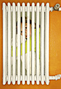 Girl crouching behind a heater - VI000149