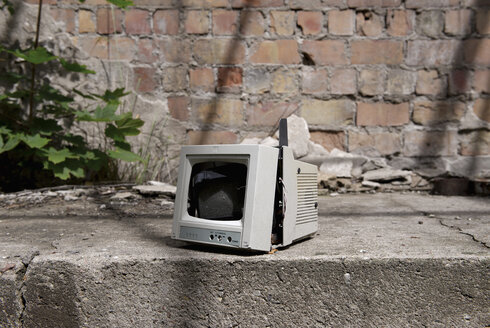 Germany, Brandenburg, Wustermark, Olympic village 1936, broken monitor in front of decaying military building - VI000075