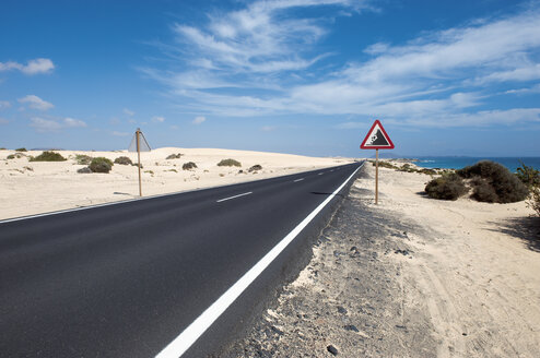 Spain, Fuerteventura, Corralejo, Parque Natural de Corralejo, view of empty road and road sign - VI000095