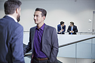 Germany, Neuss, Businessmen talking in corridor - STKF000798