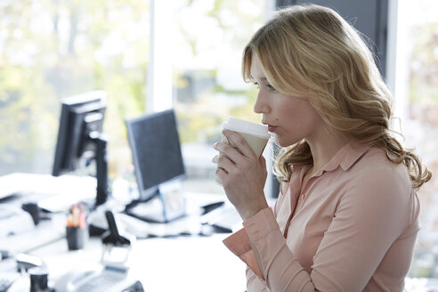 Gdermany, Neuss, Young woman in office drinking coffee - STKF000810