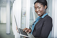 Germany, Neuss, Young Afro-european business woman using laptop - STKF000864