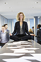 Germany, Neuss, Business woman meditating on desk - STKF000752