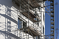 Germany, Bavaria, Munich, scaffold at facade of apartment tower - TCF003731