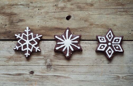 Three gingerbread stars decorated with sugar icing on wooden table - CZF000125